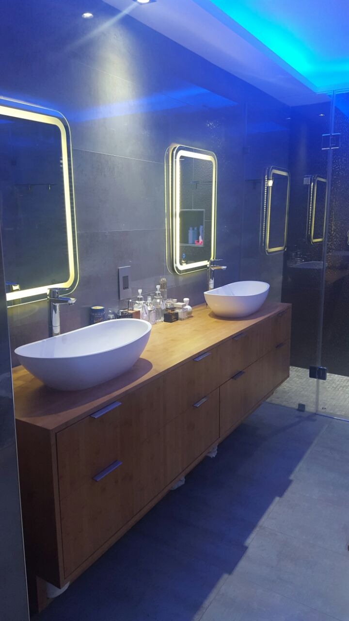 Thohira's Bathroom with Light up mirrors and blue recess LED strip lite.